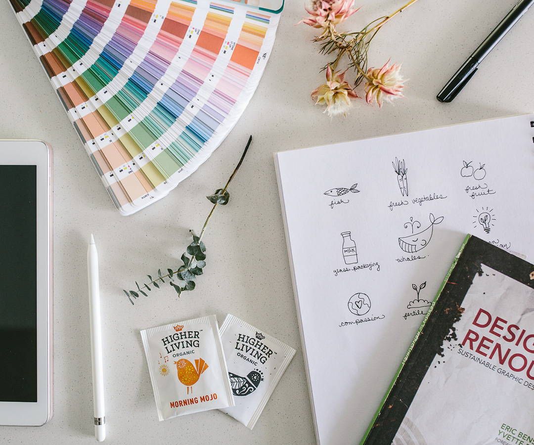 flat lay of fanned colour swatch book, sketch book and pens and resources on white desktop